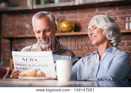 Funny joke. Nice retired couple smiling while reading a funny story