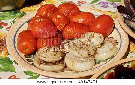 Tomatoes and onions grilled and laid on a ceramic plate with natural sunlight
