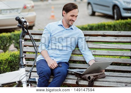 Pleasure work time . Satisfied handsome man working on laptop and smiling while sitting on the bench.