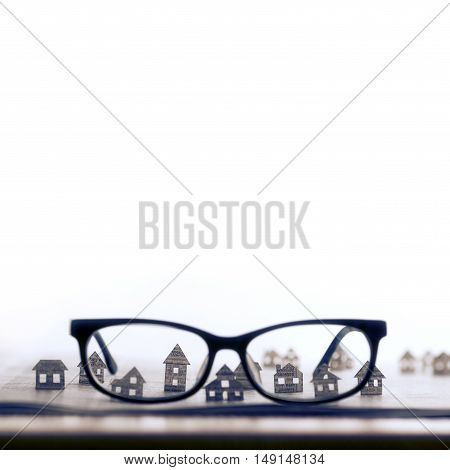 Eyeglasses lie on the open newspaper with paper houses. That could mean rent search purchase real estate. The template has lot of space for your text.
