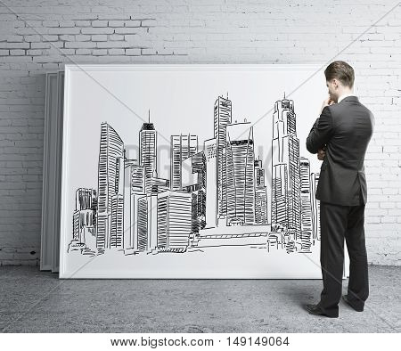 Young businessman in brick room looking at whiteboard with creative city sketch