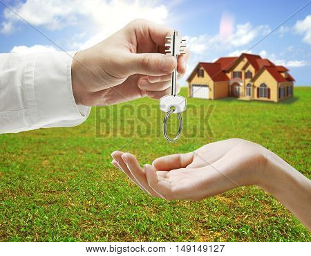 Businessman handing key to woman outside on landscape and bright sky background. Real estate and mortgage concept