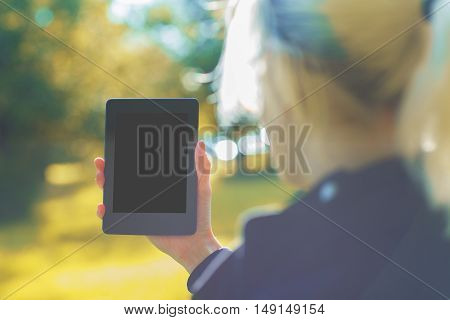 Back view of blurry woman with blonde hair standing outside and holding tablet on bright landscape background with sunlight. Mock up