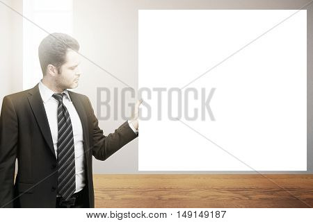 Handsome young businessman in suit and tie holding blank poster in interior. Mock up