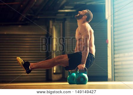 Young strong man is training by kettle bell.