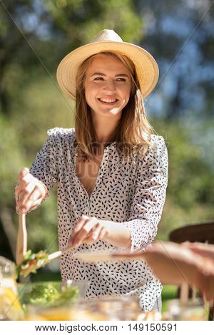 leisure, holidays, eating, people and food concept - happy young woman serving and sharing salad for dinner at summer garden party