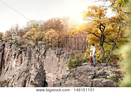 Beautiful couple in autumn nature standing on a rock against colorful autumn forest