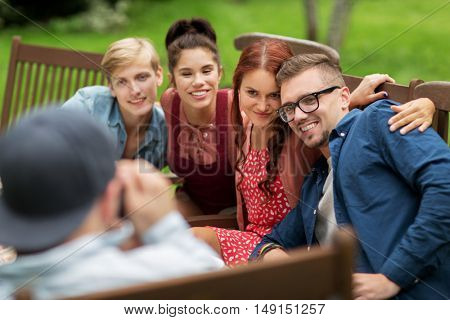 leisure, holidays, eating, people and food concept - happy friends having dinner and photographing at summer garden party