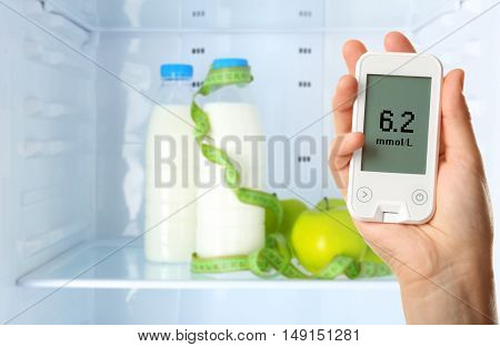 Male hand holding glucometer with food on shelf of refrigerator background. Diabetes concept