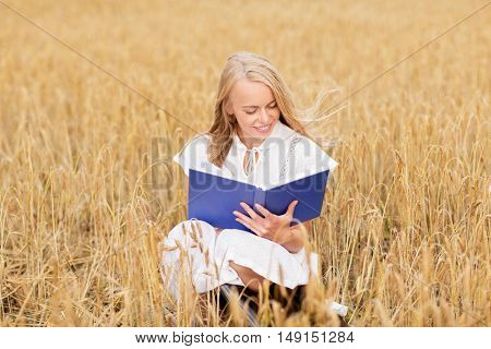 country, summer holidays, literature and people concept - smiling young woman in white dress reading book on cereal field