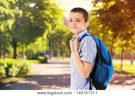 Cute boy with backpack on blurred nature background. School concept.
