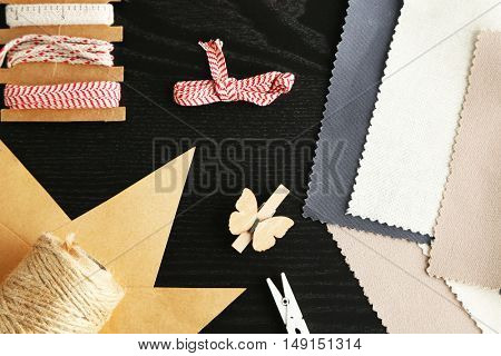 Sewing creative accessories on black wooden background, top view