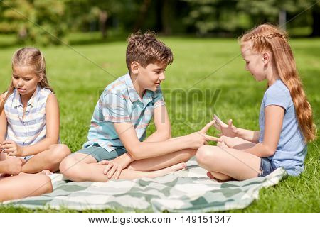summer holidays, entertainment, childhood, leisure and people concept - group of happy pre-teen kids playing rock-paper-scissors game in park