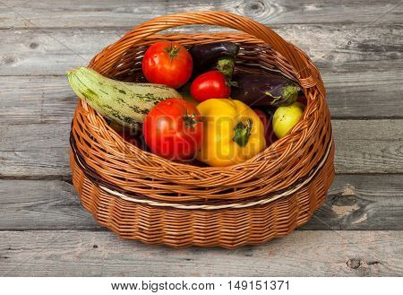Colorful vegetables in basket on old wood table