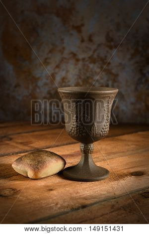 Bread and cup of wine on wooden table