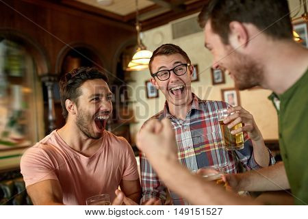 people, leisure, friendship and entertainment concept - happy football fans or male friends drinking beer and celebrating victory at bar or pub