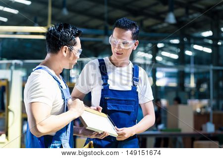 Carpenter team in Asian wood workshop checking the measurements of wooden boards