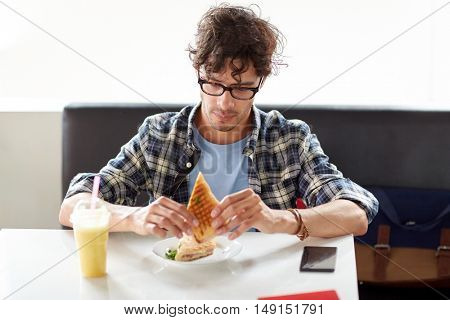 leisure, food, eating and people concept - happy man eating sandwich at cafe for lunch