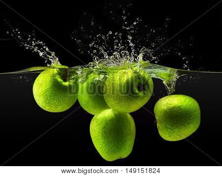 Group of green apples falling in water with splash on black background.