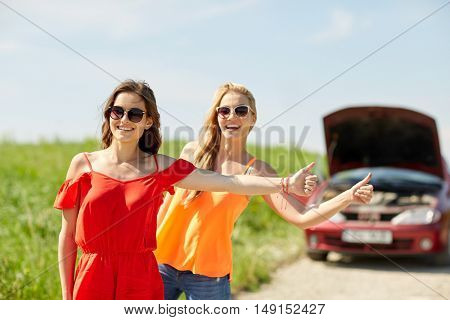 road trip, transport, travel, gesture and people concept - happy young women with broken car showing hitchhiking gesture asking for help at countryside