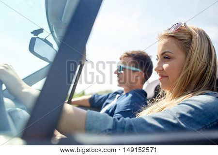 leisure, road trip, travel and people concept - happy couple driving in cabriolet car outdoors