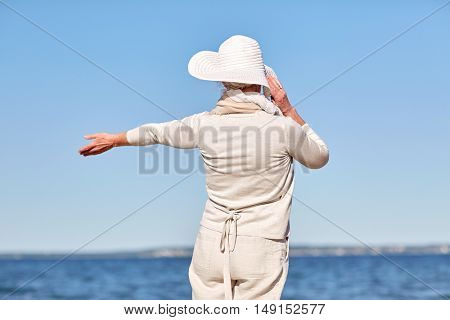 old age, leisure, travel, tourism and people concept - happy senior woman in sun hat on summer beach