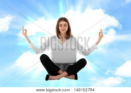 Businesswoman with laptop sitting in lotus pose against sky background. Yoga concept.
