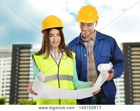 Man and woman in uniform with engineering blueprints on building construction background