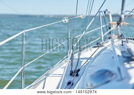 vacation, travel, cruise and yachting concept - close up of cable on sailboat or sailing yacht deck and sea