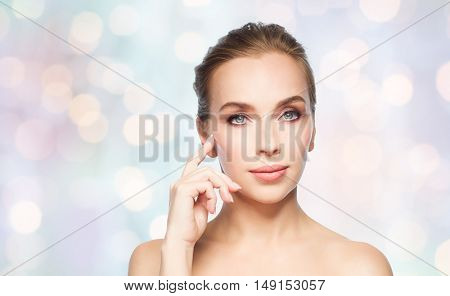 beauty, people and plastic surgery concept - beautiful young woman showing her cheekbone over blue holidays lights background