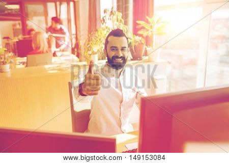 business, startup, gesture and people concept - happy businessman or creative male office worker with computer showing thumbs up