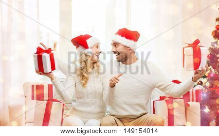christmas, holidays and people concept - happy couple in santa hats with gift boxes sitting on sofa and showing thumbs up at home over lights