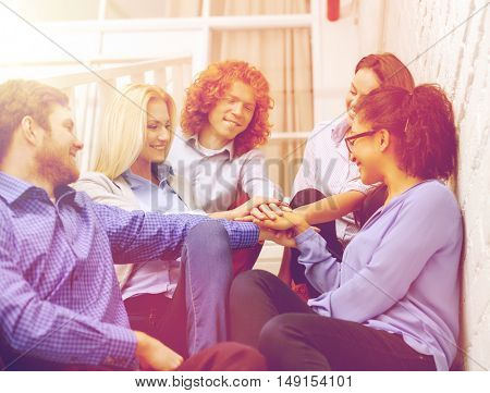 business, office, gesture and startup concept - smiling creative team with hands on top of each other sitting on staircase