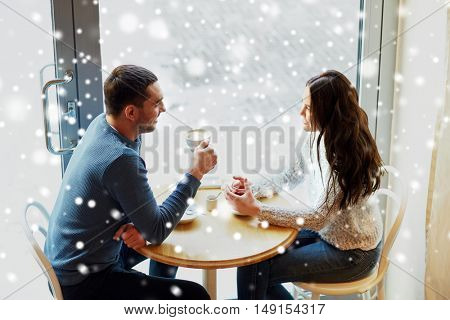 people, communication and dating concept - happy couple drinking tea and coffee at cafe