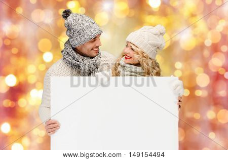 christmas, x-mas, people, holidays and advertisement concept - happy woman and man in winter clothes with blank white board over lights background