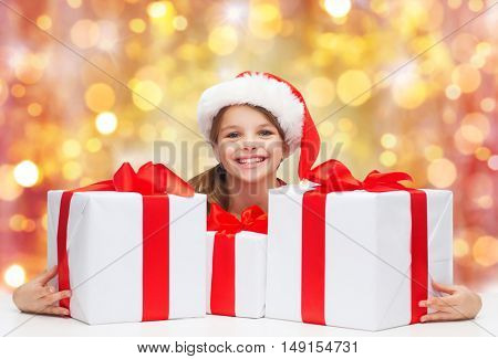 christmas, holidays, winter, children and people concept - smiling girl in santa helper hat with gift boxes over lights background