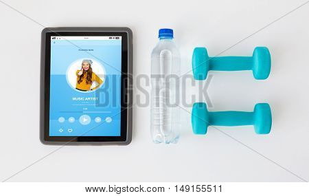 sport, healthy lifestyle, fitness, technology and objects concept - close up of tablet pc computer with dumbbells and water bottle over white background