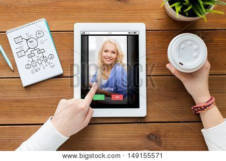 business, education, communication, technology and people concept - close up of woman with incoming call tablet pc computer screen and coffee on wooden table