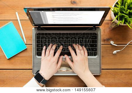 programming, business, people and technology concept - close up of woman or student typing on laptop computer with coding on screen, notebook and earphones on wooden table