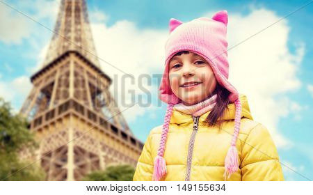 childhood, tourism, travel, vacation and people concept - happy beautiful little girl over eiffel tower in paris background