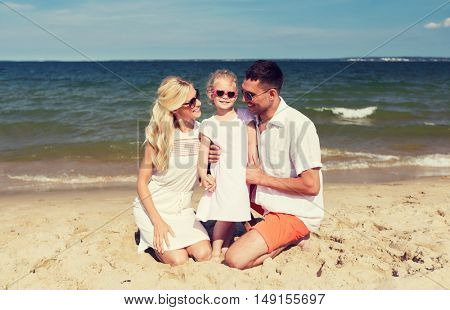 travel, vacation, adoption and people concept - happy family with little girl in sunglasses talking on summer beach