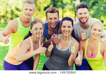 fitness, sport, friendship and healthy lifestyle concept - group of happy teenage friends or sportsmen showing thumbs up outdoors