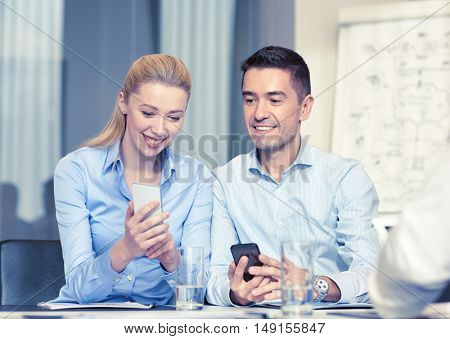 business, people and technology concept - smiling business team with smartphones meeting in office