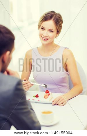 restaurant, couple and holiday concept - smiling woman eating dessert and looking at husband or boyfriend at restaurant