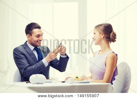 restaurant, couple, technology and holiday concept - smiling man taking picture of wife or girlfriend with digital camera at restaurant