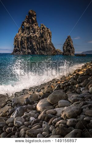 Splashing waves at stone beach of Ribeira da Janela Madeira Portugal. Majestic volcanic rocks rise from Atlantic Ocean near island coast.