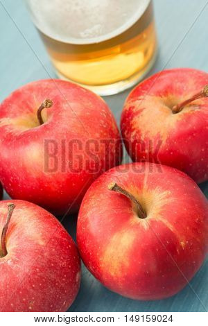 Ripe red apples with a glass of cider blue table close up