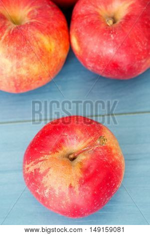 Ripe red apples on blue table close up