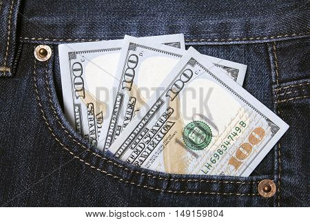 dollars invested in a pocket of dark jeans closeup