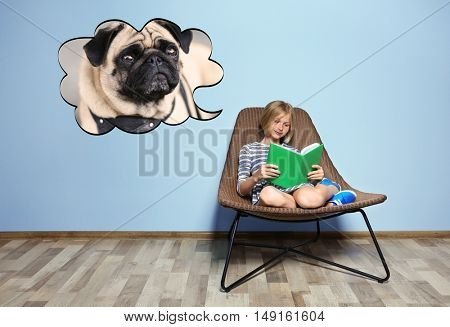 Cute girl reading book and dreaming about the dog on blue wall background